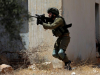 Um soldado israelita aponta a arma a manifestantes palestinos em Kafr Qaddum, Cisjordânia ocupada, 12 de Julho de 2019