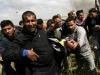 Faris al-Raqib (em primeiro plano) ajudando a socorrer um palestino ferido, antes de ele próprio ser atingido a tiro